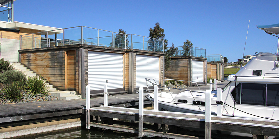 boathouse in paynesville have semi translucent polycarbonate doors. The clean white colour contrasts with the timber.