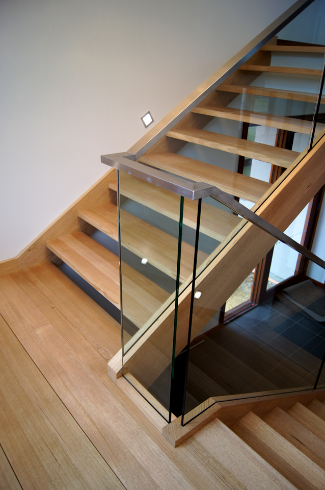The stair uses hardwood, glass and chrome in a minimalist design